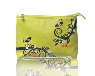 Este original neceser de viaje puede también ser usado como un práctico bolso de mano. Es de la marca Shagwear y en él podemos ver unos pájaros sobre unas ramas de árboles en los que destacan las cerezas de color rojo colgando.